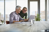 Smiling mature couple using laptop on table at home - RBF06500