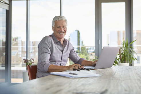 Portrait of smiling mature man using laptop on table at home - RBF06503