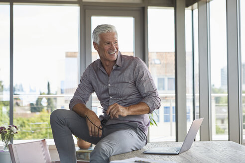 Smiling mature man with laptop sitting on table at home - RBF06506