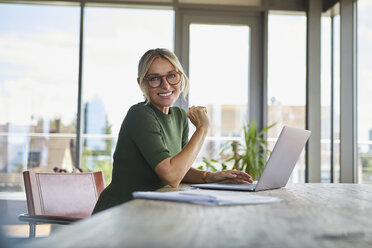 Portrait of smiling mature woman using laptop on table at home - RBF06509