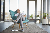 Mature man relaxing in armchair at the window at home - RBF06518