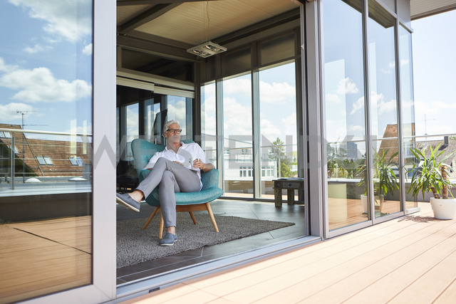 Mature man relaxing in armchair at roof terrace at home - RBF06524 - Rainer Berg/Westend61