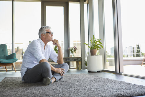 Pensive mature man sitting on carpet at home - RBF06527