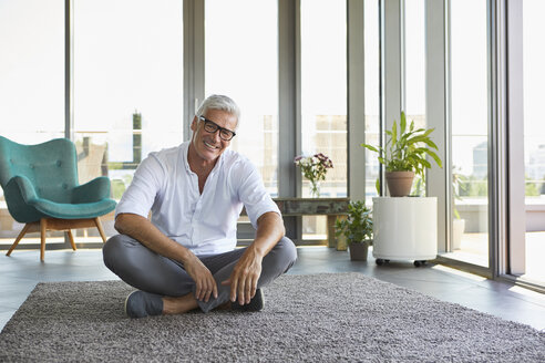 Portrait of smiling mature man relaxing sitting on carpet at home - RBF06533