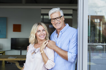 Portrait of smiling mature couple at the balcony at home - RBF06536
