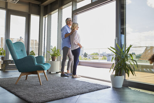 Mature couple looking out of window at home - RBF06539