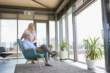 Mature couple relaxing at home looking out of window - RBF06545