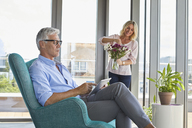 Mature couple at home with man using tablet and woman arranging flowers - RBF06548
