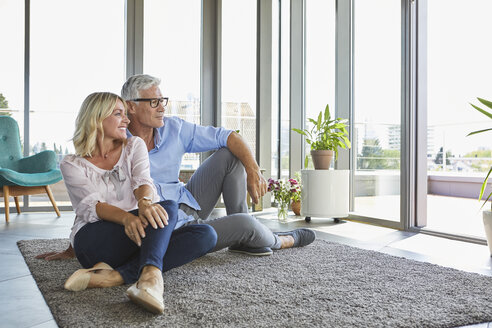 Mature couple relaxing at home looking out of window - RBF06554