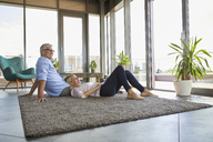 Mature couple relaxing at home on carpet - RBF06557