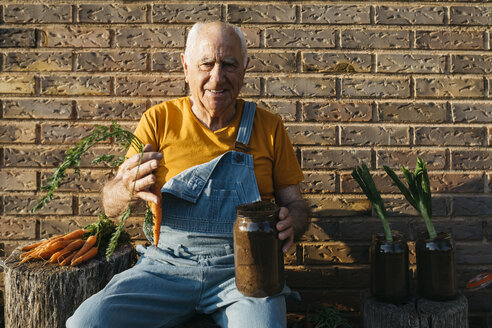 Smiling senior man with glass jars of soil and fresh carrots looking at camera - JRFF01842