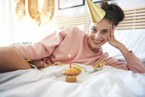 Happy young woman with cupcake during birthday - ABIF00974
