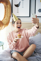 Woman blowing out the candle on the birthday cake and making a selfie - ABIF00977