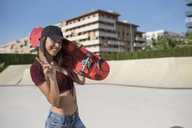 Young woman in skate park, carrying skateboard - JASF01938