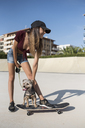 Young woman in skate park, stroking her dog, sitting on skateboard - JASF01941