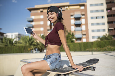 Young pretty woman sitting on wall of skatepark, listen music, using digital tablet - JASF01947