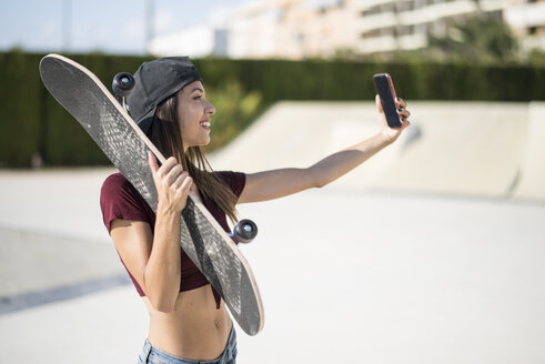 Young woman with skateboard taking a smartphone selfie - JASF01950