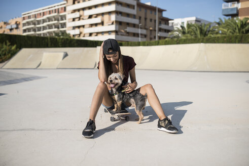 Young woman sitting on skateboard, stroking her dog - JASF01953