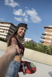 Young woman in skate park, holding hand of a man - JASF01956