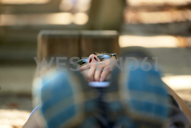 Young woman lying on park bench - JEDF00326