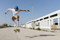 Sportive man jumping above ground with skateboard performing trick - JRFF01846