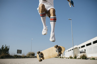 Sportive man jumping above ground with skateboard performing trick - JRFF01849