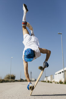 Back view of man in stylish sportive outfit standing on skateboard upside down against blue sky - JRFF01852