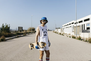 Portrait of sportive man in white and blue with skateboard on empty gray paved road - JRFF01858