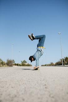 Trendy man in denim and cap skateboarding, standing on skateboard upside down - JRFF01864