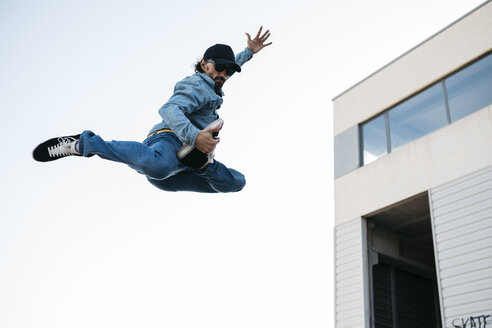 Trendy man in denim and cap doing jump - JRFF01867