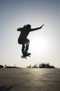 Sportive man jumping above ground with skateboard performing trick - JRFF01870