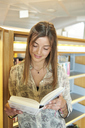 Portrait of smiling young woman with  book at the library - IGGF00566