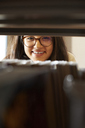 Portrait of smiling young student looking through bookshelf in the library - IGGF00575
