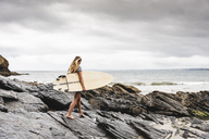 Young woman carrying surfboard on a rocky beach at the sea - UUF15036