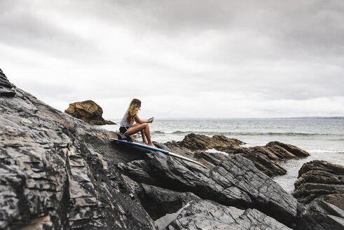 Young woman with surfboard sitting on the beach, using smartphone - UUF15039