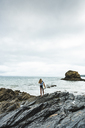Young woman carrying surfboard on a rocky beach at the sea - UUF15042