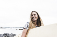 Young woman on the beach carrying surfboard, portrait - UUF15045