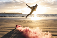 Man doing movement training at the beach with colorful smoke at sunset - UUF15057