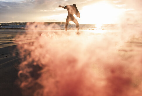 Man doing movement training at the beach with colorful smoke at sunset - UUF15060