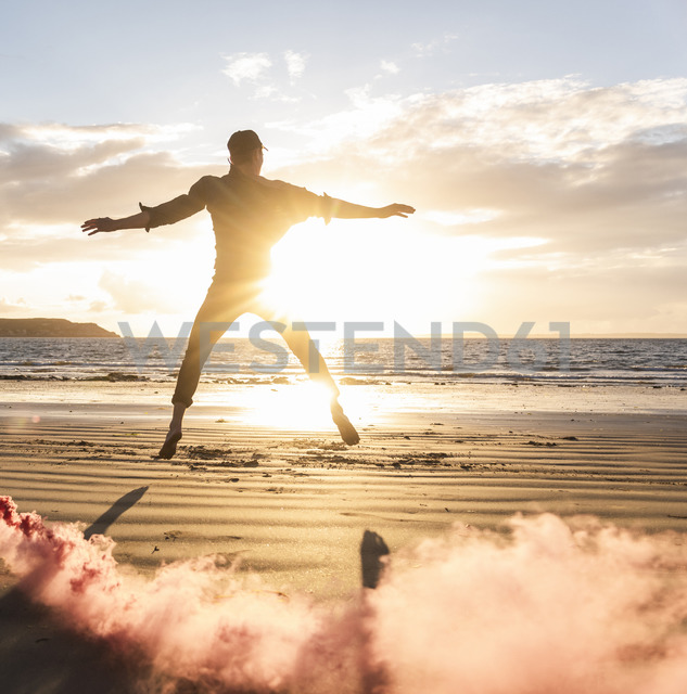 Man doing movement training at the beach with colorful smoke at sunset - UUF15063