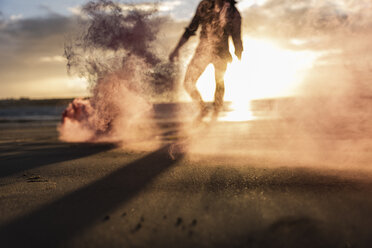 Young man running on the beach at sunset with colorful smoke - UUF15066