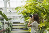 Young woman in greenhouse, taking pictures with an instant camera - KKAF01670