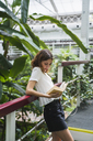 Young woman in greenhouse, reading book - KKAF01673