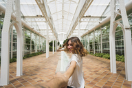 Woman holding hand ofc man in greenhouse - KKAF01682