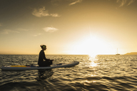 Young woman meditationg on paddleboard at sunset - UUF15068