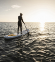 Young woman stand up paddle surfing at sunset - UUF15071