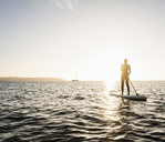 Young woman stand up paddle surfing at sunset - UUF15074