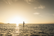 Young woman stand up paddle surfing at sunset - UUF15077