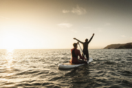 Couple on paddling on paddleboard at sunset on the sea - UUF15080
