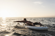 Young man on paddleboard at sunset - UUF15083